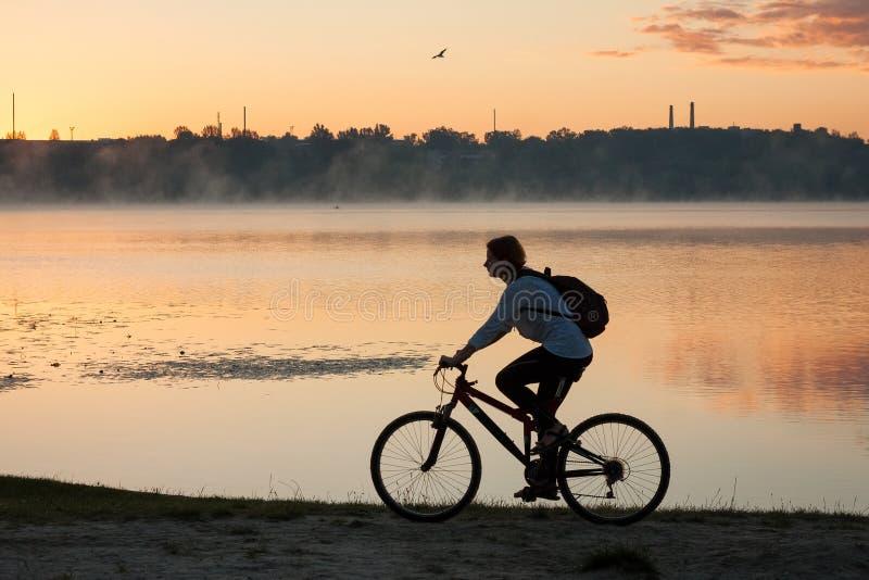 Uma menina que monta uma bicicleta perto do lago na manhã do verão imagem de stock royalty free