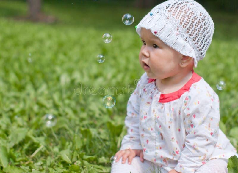 Uma menina que olha bolhas de sabão foto de stock