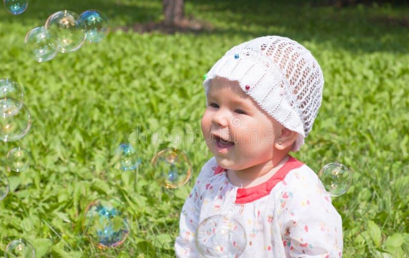 Uma menina que olha bolhas de sabão fotografia de stock