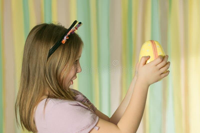 Uma menina que olha com surpresa no ovo da páscoa fotos de stock