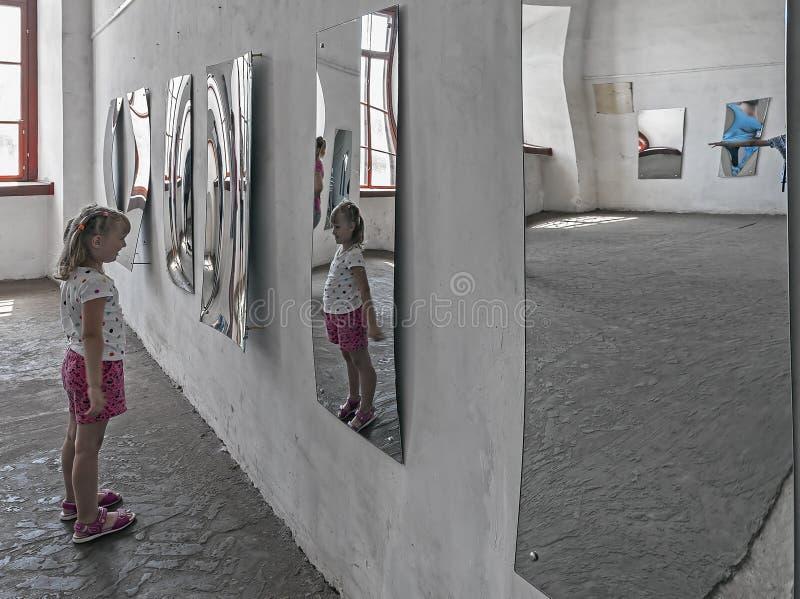 Uma menina que olha sua imagem no espelho distorcido no salão dos espelhos imagens de stock royalty free