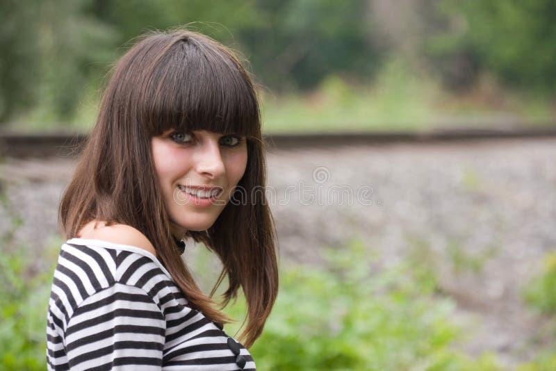 Uma menina que prestam atenção para trás e sorriso fotografia de stock