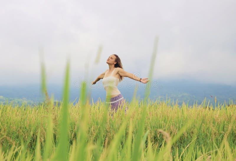 Uma menina que respira profundamente no campo do arroz imagem de stock