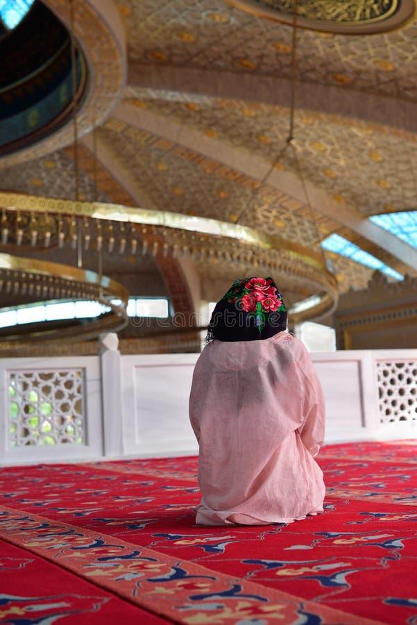 Uma menina que reza em uma mesquita fotografia de stock