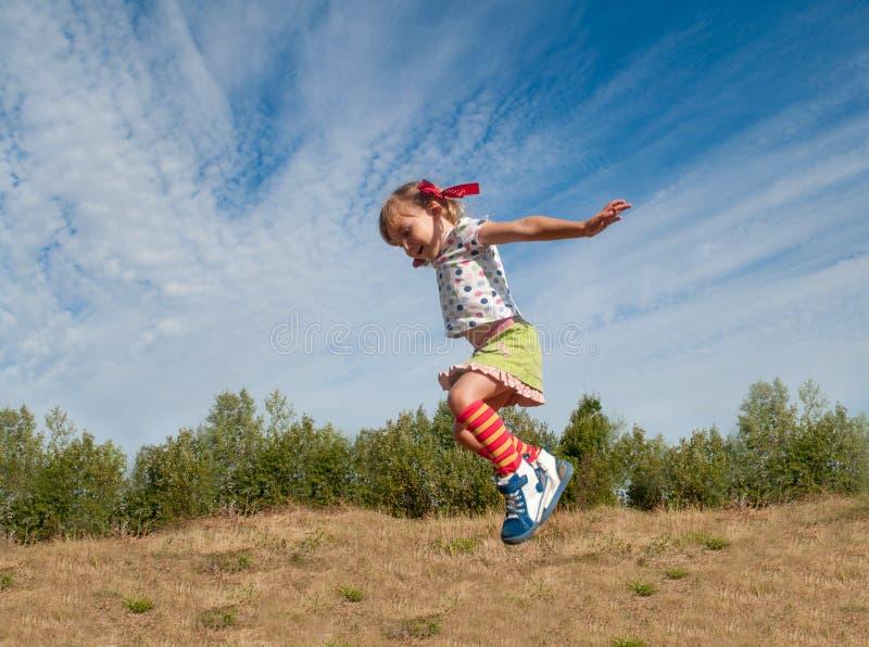 Uma menina que salta contra o fundo do céu azul imagem de stock