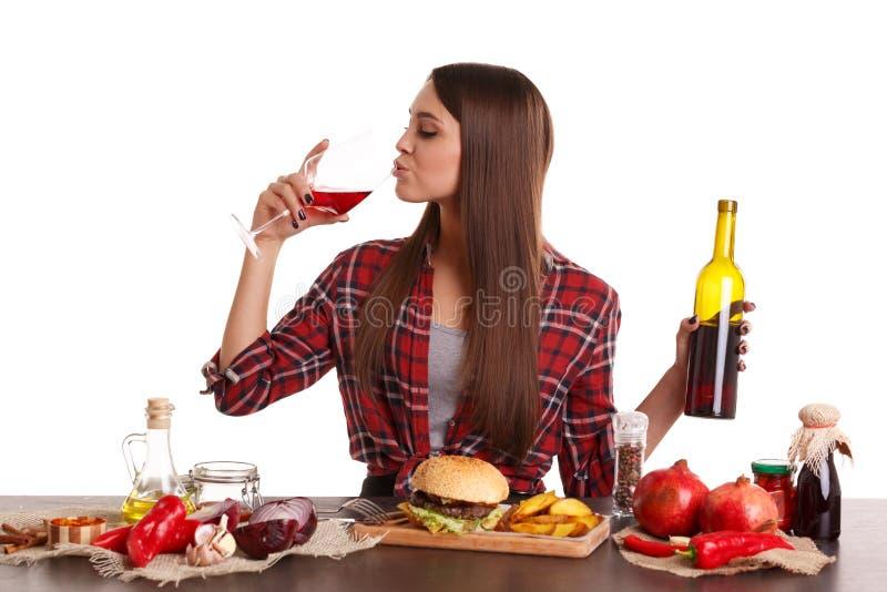 Uma menina que senta-se em uma tabela com alimento, vinho tinto bebendo de um vidro e guardando uma garrafa do vinho tinto fotografia de stock