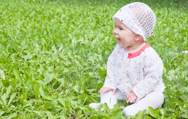 Uma menina que senta-se na grama verde foto de stock royalty free