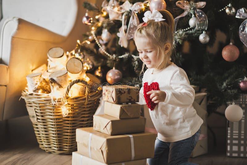 Uma menina que senta-se sob a árvore de Natal com presentes 7248 fotografia de stock royalty free