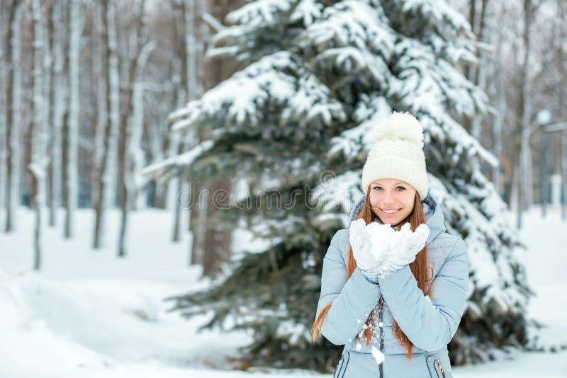 Uma menina que veste a roupa morna do inverno e a neve de sopro do chapéu na floresta do inverno, horizontal Modele com um sorris fotos de stock royalty free