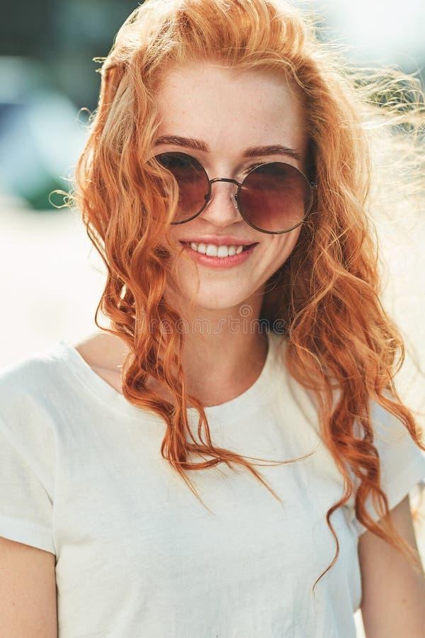 Uma menina ruivo bonita em um t-shirt branco e em caminhadas dos óculos de sol abaixo da rua e dos sorrisos no quadro fotos de stock