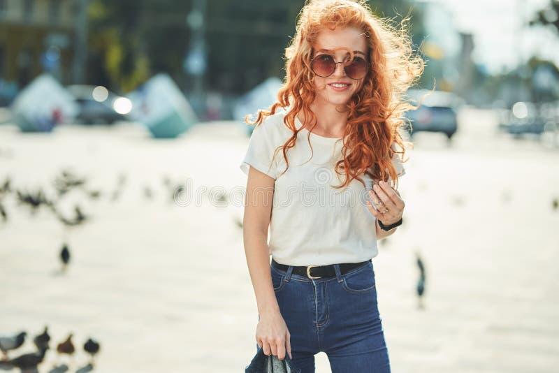 Uma menina ruivo bonita em um t-shirt branco e em caminhadas dos óculos de sol abaixo da rua e dos sorrisos no quadro imagens de stock