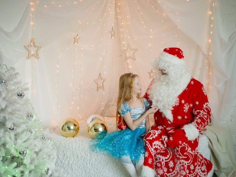 Uma menina ruivo bonita toca em sua barba branca na véspera de Ano Novo de Santa ` S do ano novo e Natal fotografia de stock royalty free