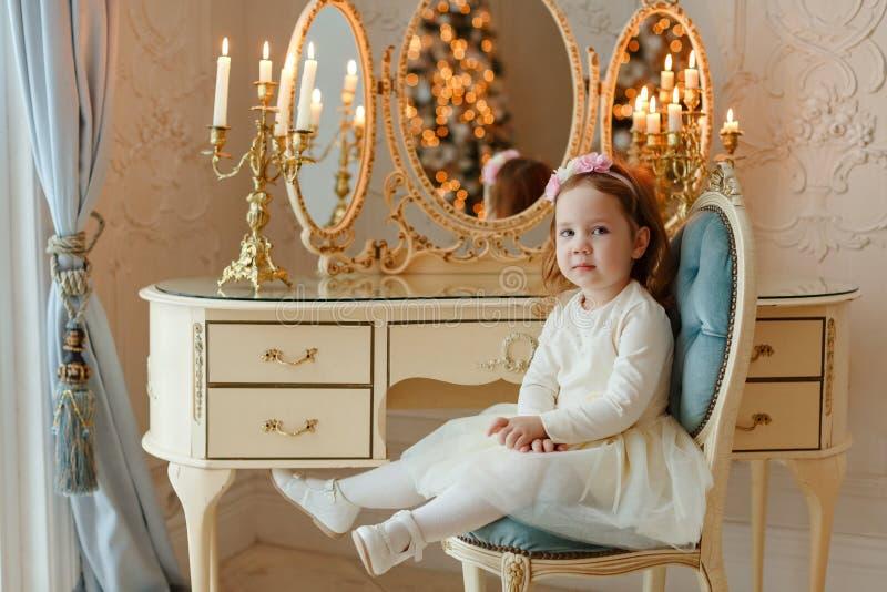 Uma menina ruivo pequena está sentando-se na tabela de molho e olha o quadro Contra o contexto do ` do ano novo s ilumina-se imagens de stock royalty free