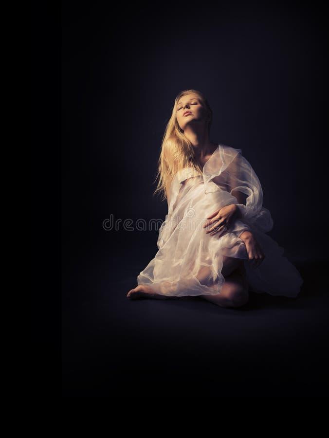 Uma menina semi-nua bonita no roupa translúcida branca na fotos de stock