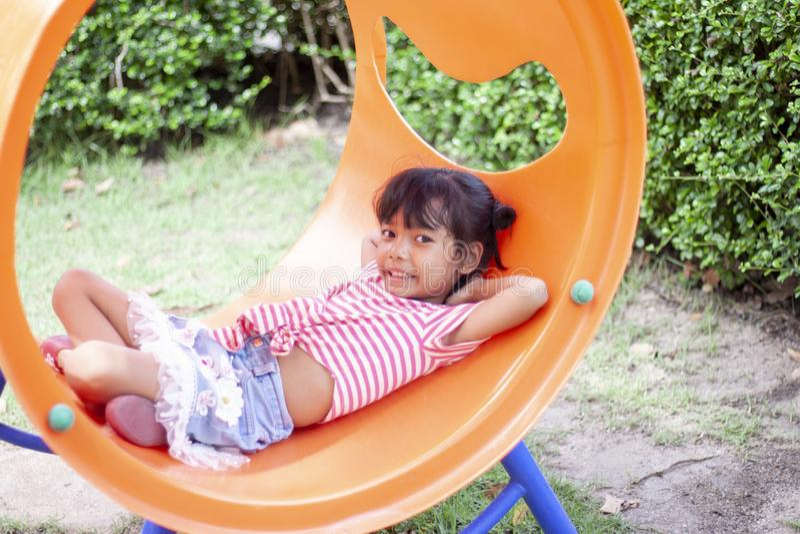 Uma menina senta descansadamente no campo de jogos no feriado foto de stock