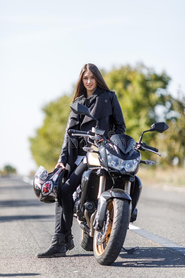 Uma menina senta-se em uma motocicleta na roupa de couro preta fotos de stock royalty free