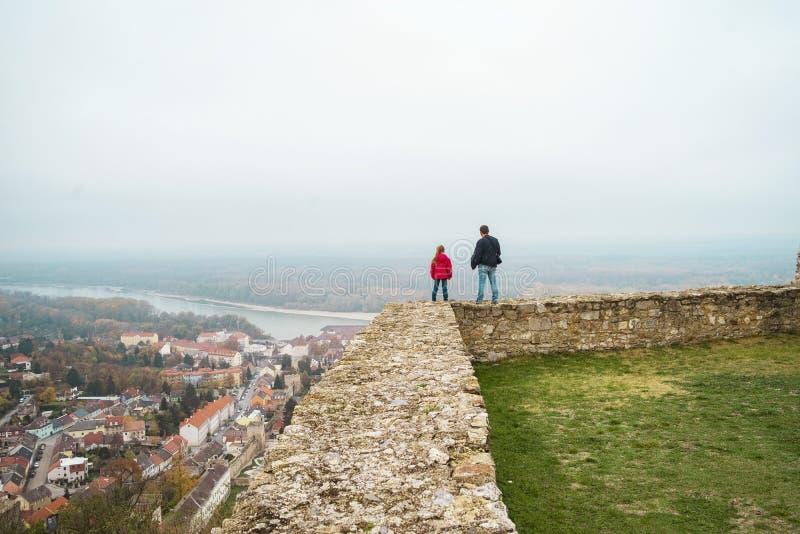 Uma menina senta-se em uma parede velha da rocha A menina que senta-se nas etapas no castelo velho imagem de stock royalty free