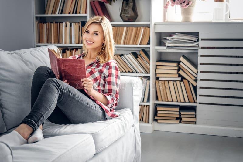 Uma menina senta-se em um sofá e lê-se um livro em uma sala de visitas fotografia de stock royalty free