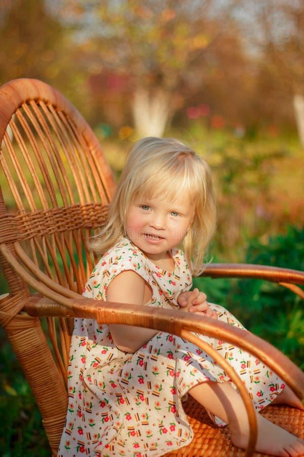Uma menina senta-se em uma cadeira fora fotos de stock royalty free