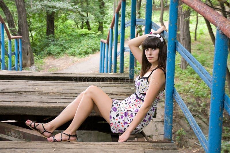 Uma menina senta-se em uma ponte imagem de stock royalty free