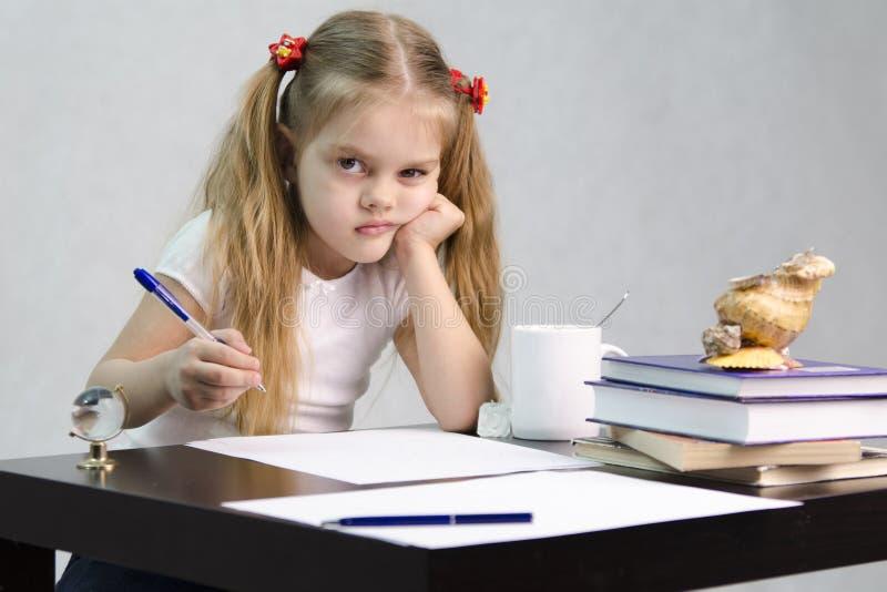 A menina escreve em um pedaço de papel que senta-se na tabela na imagem do escritor imagem de stock royalty free