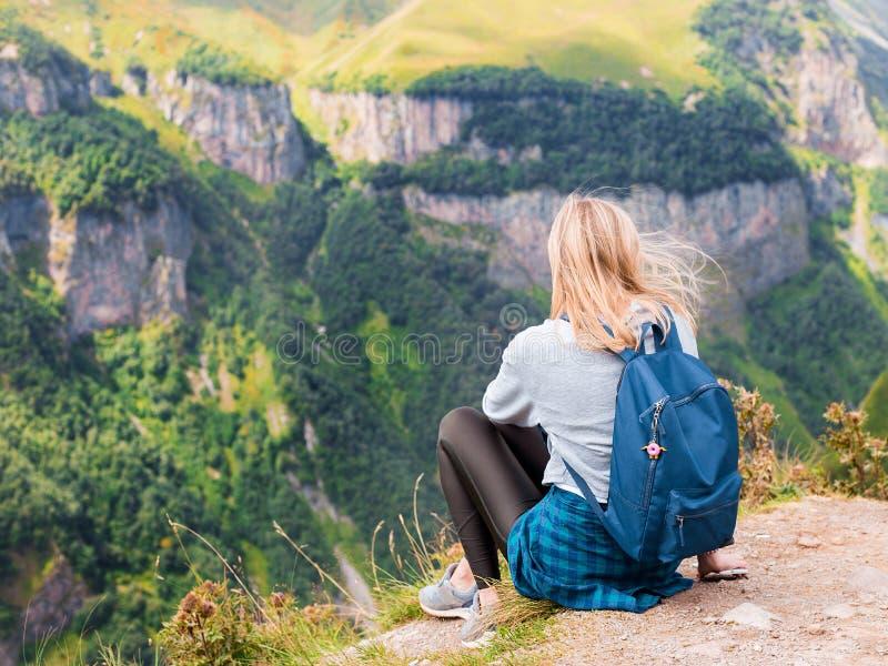 Uma menina senta-se na borda do penhasco e de olhar o vale Mulher que aprecia a opinião da floresta da parte superior do foto de stock