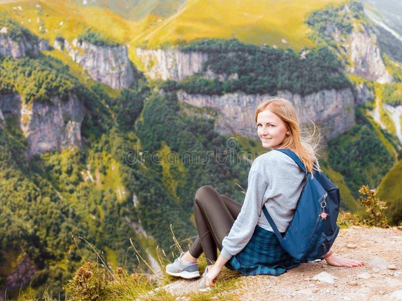 Uma menina senta-se na borda do penhasco e de olhar o vale Mulher que aprecia a opinião da floresta da parte superior do fotografia de stock
