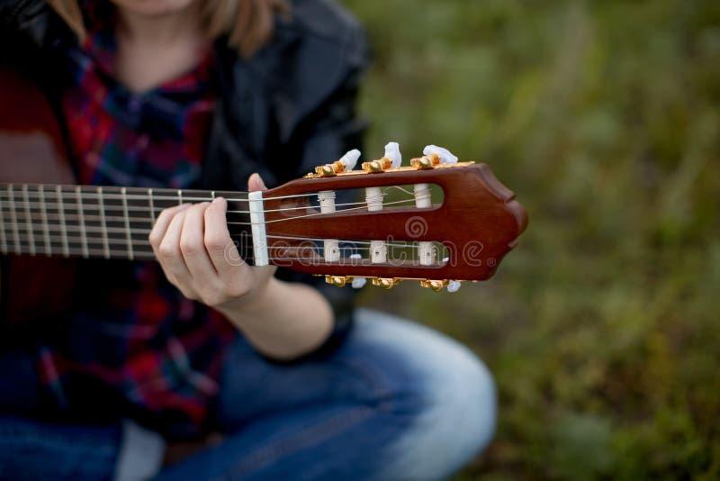 Uma menina senta-se na grama com um jogo da guitarra, pondo sua mão fotografia de stock