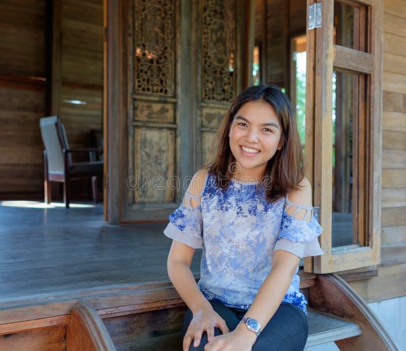 Uma menina tailandesa que sorri em sua casa de madeira fotografia de stock royalty free