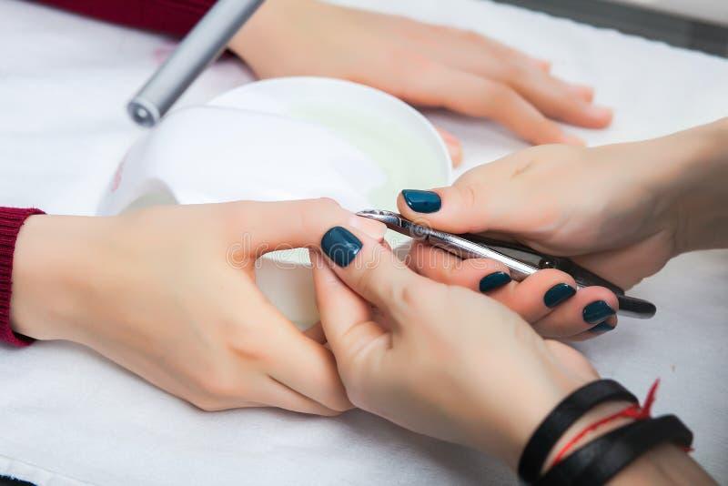 Uma menina tem um tratamento de mãos em um salão de beleza, limpando a cutícula imagens de stock