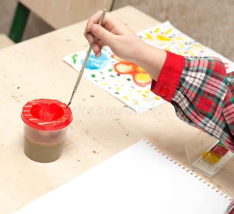 Uma menina tira um desenho com pinturas em uma folha fotos de stock