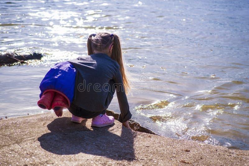 Uma menina toca no rio com sua mão Uma menina pelo rio em um dia ensolarado fotos de stock royalty free