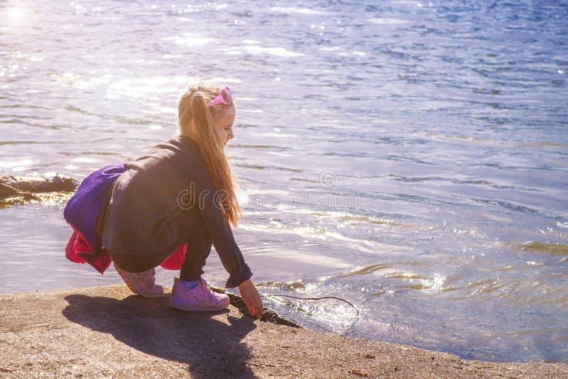 Uma menina toca no rio com sua m?o Uma menina pelo rio em um dia ensolarado imagens de stock