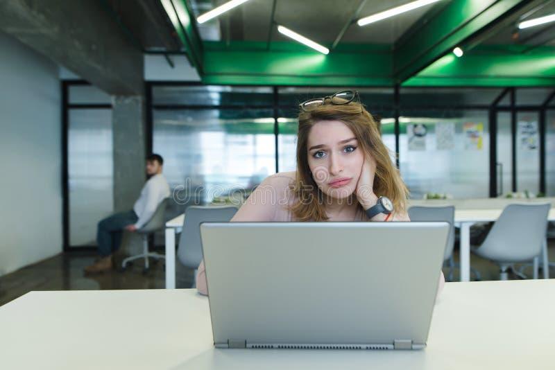 Uma menina triste com uma xícara de café em suas mãos usa um portátil na mesa no escritório imagem de stock royalty free