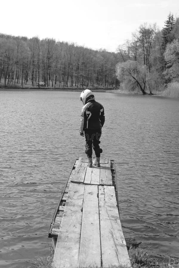 Uma menina triste está estando apenas no cais pelo lago Fundo da floresta vestir no equipamento da proteção do equipamento da mot foto de stock