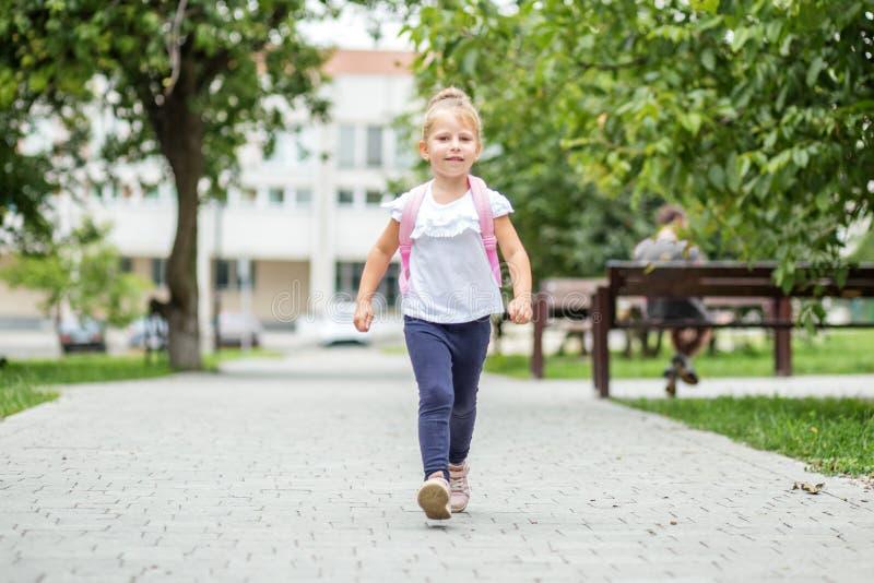 Uma menina vem com uma trouxa para lições O conceito da escola, estudo, educação, amizade, infância fotos de stock
