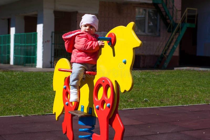 Uma menina vestida em um revestimento cor-de-rosa está sentando-se em um cavalo amarelo do brinquedo Os jogos do bebê no campo de imagens de stock royalty free