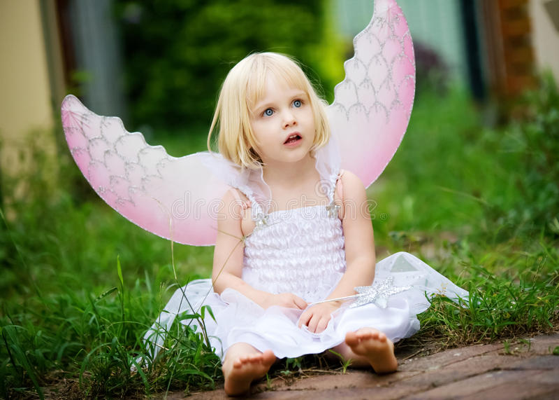 Uma menina vestida em um traje do anjo imagem de stock