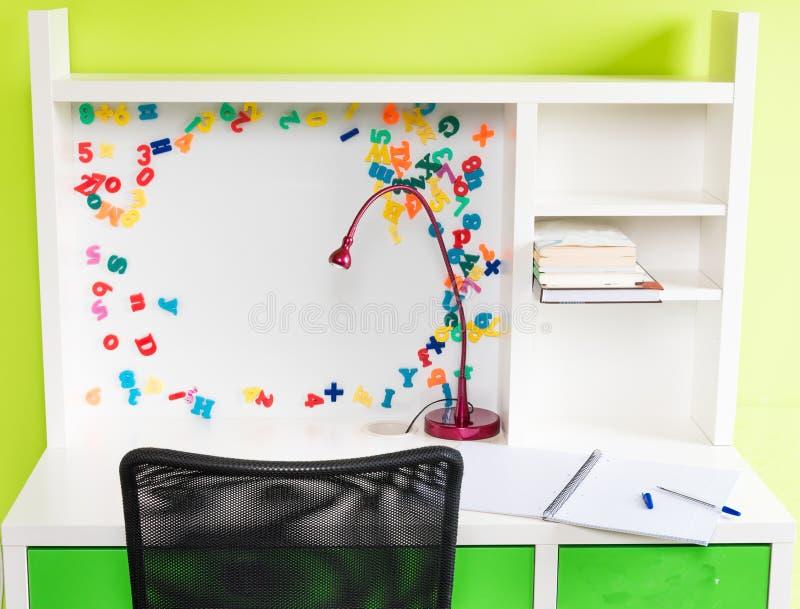 Uma mesa da escola do ` s da criança com fontes de escola imagens de stock