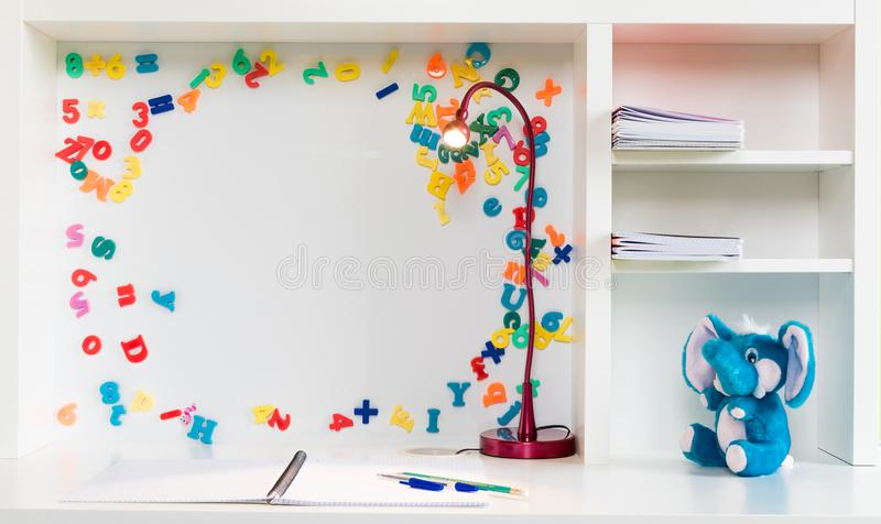 Uma mesa da escola do ` s da criança com fundo branco, letras coloridas e números, pena, lápis, elefante encheu o brinquedo foto de stock royalty free