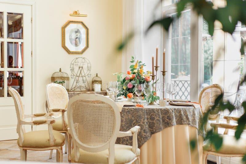 Uma mesa de jantar e umas poltronas confortáveis em uma casa moderna com uma sala de jantar clara imagem de stock