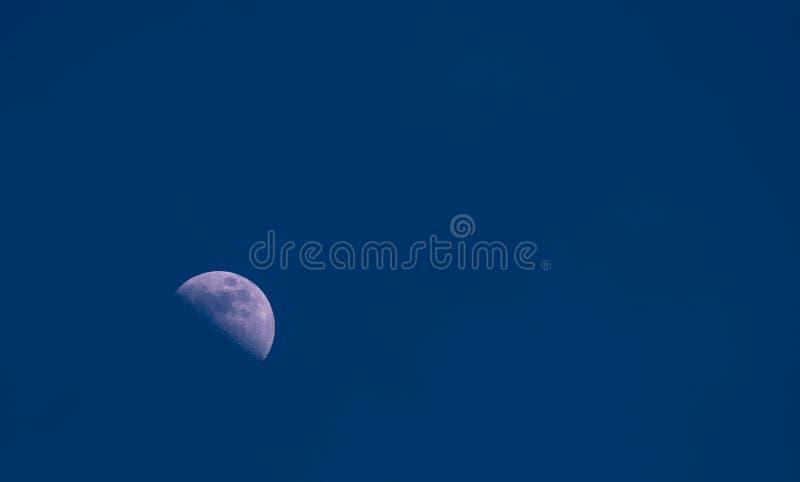 Uma metade do fim da lua acima na obscuridade, a noite, o céu azul, as crateras e a estrutura da lua são visíveis fotografia de stock