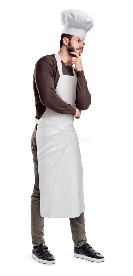 Uma metade-volta considerável nova da posição do cozinheiro chefe e levantamento com mão em seu queixo como se pensando sobre alg imagem de stock
