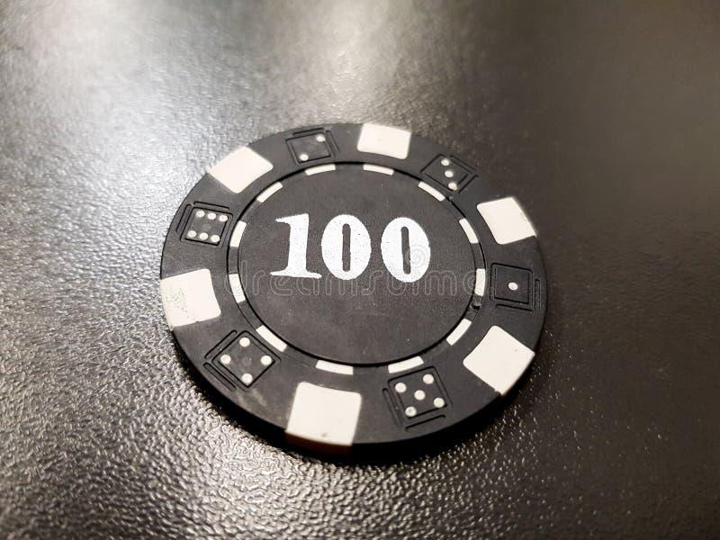 uma microplaqueta de pôquer preta de 100 em uma tabela preta foto de stock