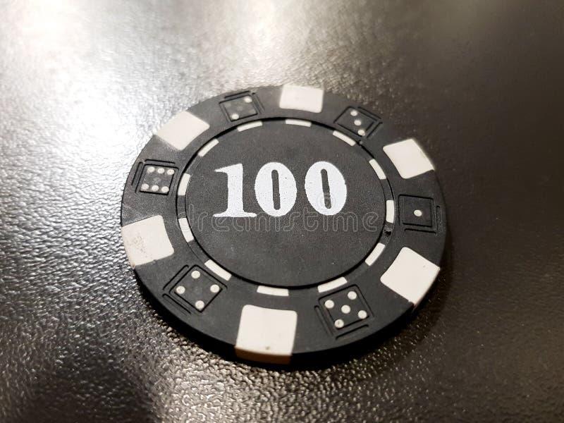 uma microplaqueta de pôquer preta de 100 em uma tabela preta imagem de stock