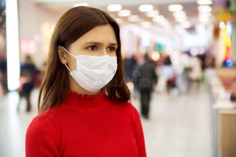 Uma moça alarmada olha de sobrancelhas franzidas e olha afastado está na alameda e está receosa da infecção fotografia de stock