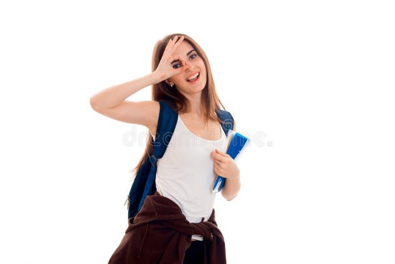 Uma moça alegre no t-shirt e com uma trouxa no olho do ombro fecha a mão fotos de stock