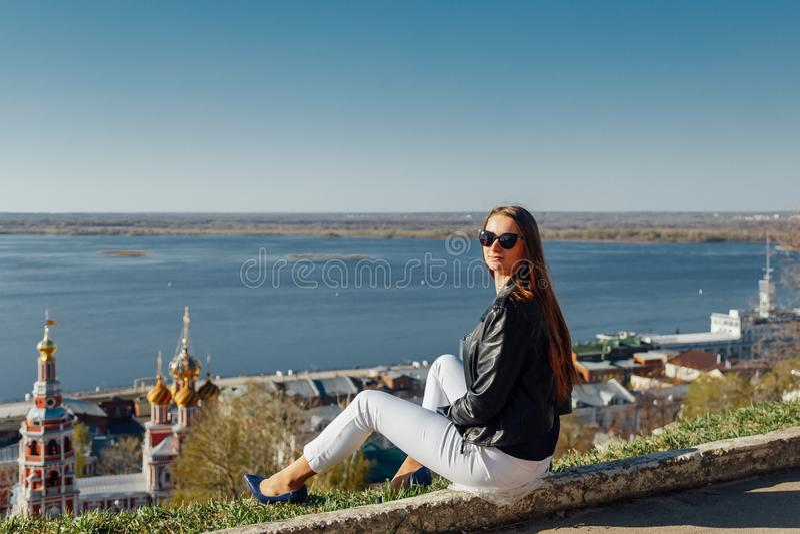Uma moça anda na terraplenagem da baía da cidade foto de stock