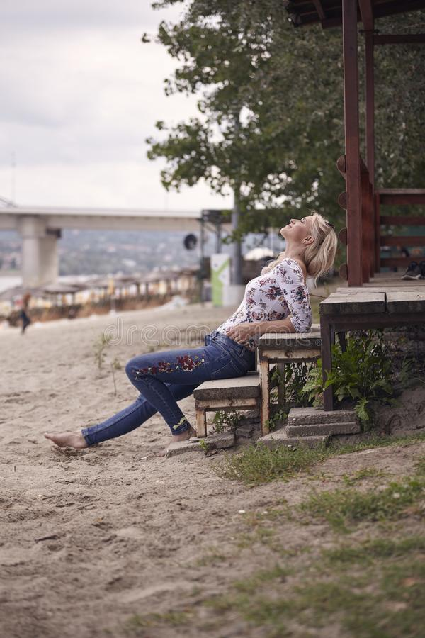 uma moça, 25 anos velha, sentando-se em etapas na areia da praia, verão, sorriso feliz, olhando acima acima, fora, a vista latera foto de stock