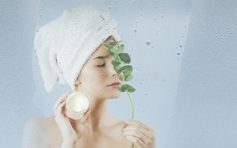 Uma moça após ter tomado um banho usa um creme hidratando do corpo e de cara em um fundo azul O conceito dos cuidados com a pele fotografia de stock